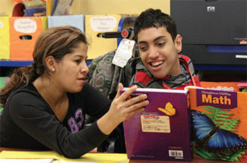 Male NJEDDA high school student working on reading with female teacher = private special education school in Passaic NJ